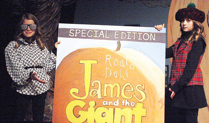 "Allyson Russell and Elizabeth Russell hold up a life sized copy of the book ""James and the Giant Peach."""