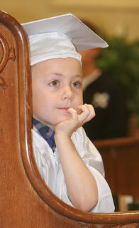 Kindergartner Avery Adams waits patiently to receive his certificate.
