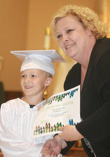 Kindergartner Lane Buckman accepts his diploma from teacher Cindy Bland.