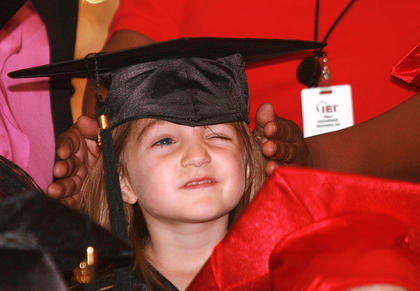 Preschooler Grace Finley makes a face as Laura Furmon adjusts her cap.