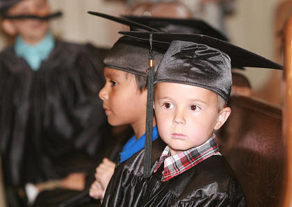 Preschoolers Matthew Gaddie, right, and Max Castillo wait for their turn to get their certificates.