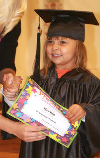 Preschooler Mya Hill grins while accepting her certificate.