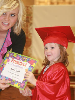 Hailey Creed accepts her certificate from preschool teacher Kaitlyn Mattingly.