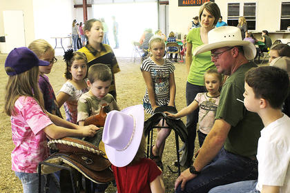 Barry Gordon talks saddles with a group of prospecting 4-H children.
