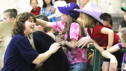 Melanie Gordon talks to a cowgirl while letting children pet a horse.