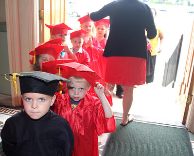 Lane Dougherty (in the black cap and gown) and John Richard Edelen (in the red cap and gown) stand patiently as their classmates get lined up before the graduation ceremony begins.