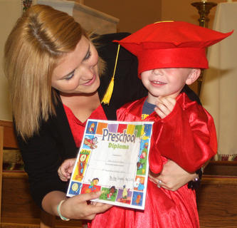 Preschool teacher Hope Newton-Dougherty hands John Richard Edelen his diploma as his graduation cap slides over his eyes.