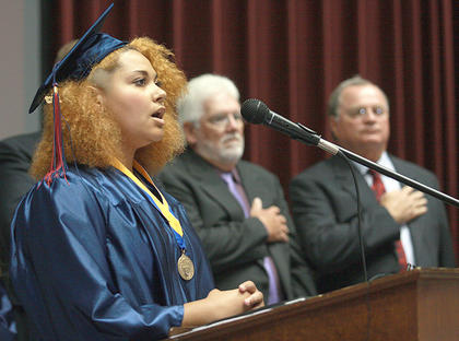Morgan Bell sings the national anthem to open the graduation ceremony. School board members Ed Hacker and Mike Cecil are in the background.