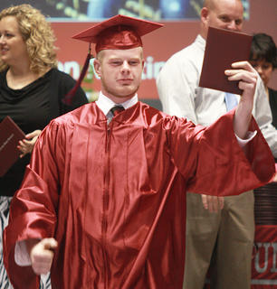Levi Mattingly holds up proof that he is a graduate.