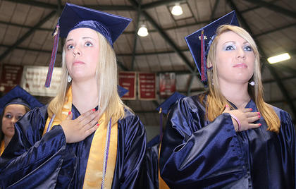Ann Rachael Bell (left) and Ashley Barlow hold their hands over their hearts during the national anthem.