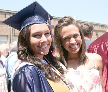 Graduates Sydney Abell, left, and Megan Caldwell stop in the crowd for a picture together.
