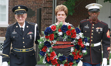 Frances Gordon carries a ceremonial wreath in honor of her husband Leo Gordon, who was the last Marion County veteran interred at Lebanon National Cemetery. She is escorted by Jim Bob Moore, left, and David Thompson.