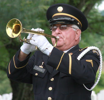 "Joe Taylor plays ""Taps"" after a three-round volley was fired to honor Marion County's fallen veterans."
