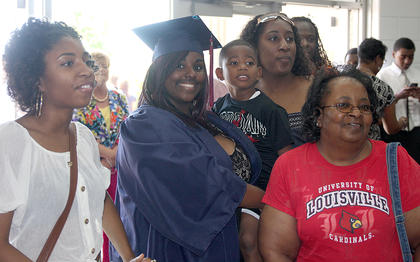 Graduate Shanda Washington poses for a picture surrounding by family members. She is holding her cousin, Kahari Adams, 4.  At left is her cousin Daija Adams, and her cousin Tiffany Adams and her grandmother, Diane Adams, are on the right