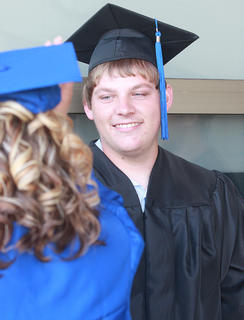 Before the ceremony begins, Hunter Livers smiles while chatting with one of his fellow graduates.