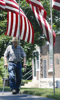 One of many visitors makes his way into the cemetery before the ceremony begins Sunday.