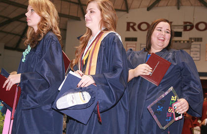From right, Haley Spalding, Bailey Spalding and Leslie Smothers exit the gym at the end of the ceremony.