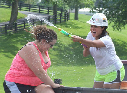 Samantha Garrett, left, looks for more balloons while Ashley Thomas attempts to spray water at her opponent.