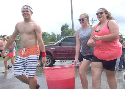 From left, seniors Trevor Hood, Katlin Masterson and Samantha Garrett take advantage of the juniors' retreat to advance a bucket of balloons.