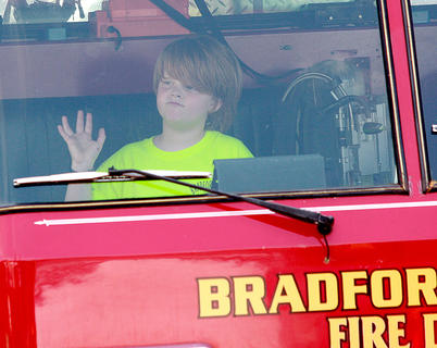 During the parade, Dylan Wiser, 8, waves to the crowd from the front seat of a Bradfordsville fire truck.