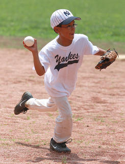 Elijah Kirkland of the Yankees throws to first for an out in the kids baseball game.
