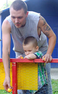 Adam Powell and his son Easton, 3, tried to hit a baby bunny by tossing ping pong balls in a glass bowl.
