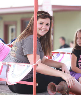 Taylor Mitchell smiles at the crowd from a parade float. Bethany Purdom is in the background.