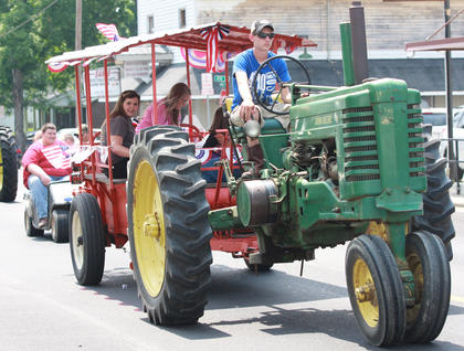 John Robert Purdom pulls a float while driving a tractor in the parade.