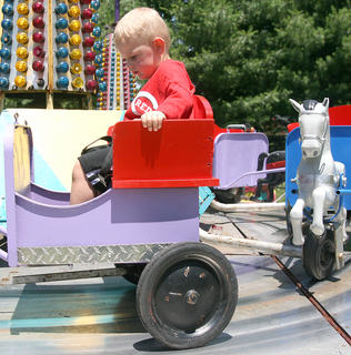 Wesley Purdom, 2, enjoys a ride on a mechanical horse-drawn carriage.