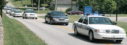 Police cars escort Bell to the St. Augustine Cemetery.
