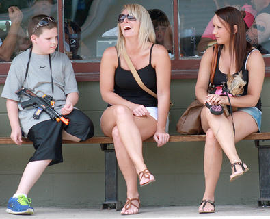 Hunter Godbey, 11, Amy Godbey and Shanna Bickett, who is holding Bella the dog, chat in the shade while waiting for the parade to begin.