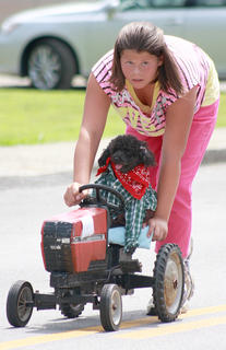 Bear drives a tractor in the Old Mill Days parade with a little help from Virginia Phillips, 12.