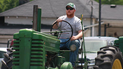 Aaron Bright drives a tractor in the Old Mills Days parade Saturday afternoon.
