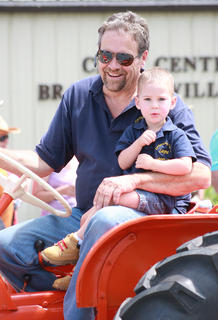 Rodney Gribbins and Layne Mattingly, 2, go for a ride on a tractor in the Old Mill Days parade.