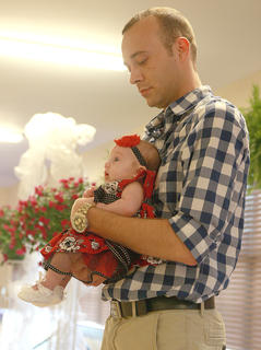 Shane Richardson holds his niece Cherish Hall during the 0-5 month old girls division in the beauty contest. Cherish is the daughter of Lean and Richard Shepperson.