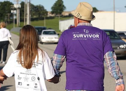 David Buckman holds hands with one of his biggest fans during the survivors' lap.