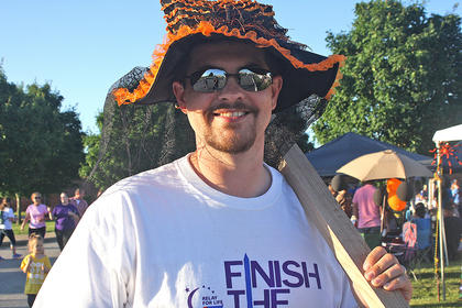 "Johnny Gordon, a member of the Kentucky Cooperage team, gets into this year's Relay for Life theme ""Scare Cancer Away"" as he wears a witch hat while walking a lap. The team had a bet as to who would be brave enough to wear the witch hat and hold a stave while walking around the track."