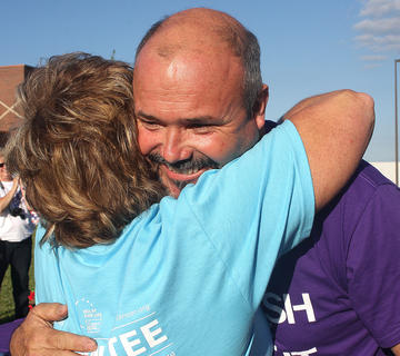 Joe Lamkin gets a big hug from Liz Lawson, Marion County Relay for Life co-chair, during the survivors' ceremony.