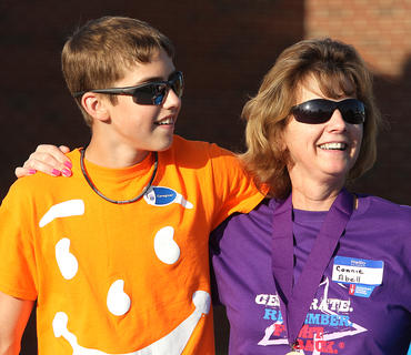 Thomas Abell and his mother, Connie Abell, walk together during the caregivers' lap.