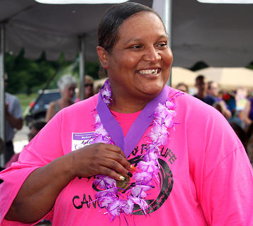 Annette Bell smiles as she proudly holds her survivor's medal.