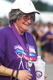 Barbara Blandford grin at the crowd as she walks during the survivor's lap.