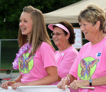 "Claire Higdon and her grandmother, Judy D. Tharp, share a laugh during the team lap at Relay for Life. Also pictured is Judy K. Tharp. They are all members of the ""12 Kids for a Cure"" team."