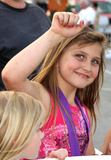 "Kaylee Buckman pumps her fists to the music as she walks with her team, ""Pulling for a Cure."""