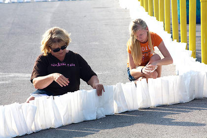 Carolyn Edberg, left, and Mary Brahm help prepare the luminaries.