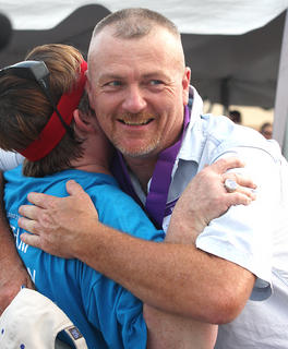 Mike Ford gets a big hug from Donna Peterson during the survivor's medal ceremony.