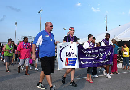 From left, Jeff Robbins, Missy Colvin, Lori Jo Milby, and Porgie Hayden held the survivors' banner and led the survivors' lap during Relay for Life.