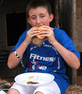 Devan Jones, 13, enjoys a ribeye sandwich that was prepared by the Marion County Cattlemen's Association.
