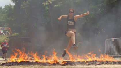 A Warrior Dash participant leaps over the Warrior Roast near the end of the race.