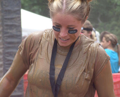 Rebecca Rhoades of Bowling Green is covered in mud after crossing the finish line. She ran the race with her fiance Keaton May.
