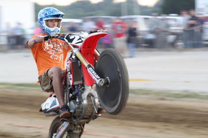 Kyle Rogers pops a wheelie as a rips past the crowd during the ATV racing at the fair on Thursday night.